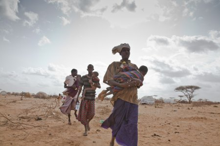 Somali refugees in Dadaab refugee camp carry their sick and malnourished children to a new feeding center