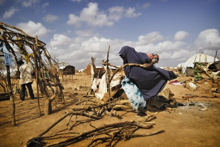 A woman is building a shelter in Dadaab refugee camp