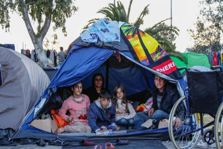 A man and his children are under a tent in Piraeus port in Athens