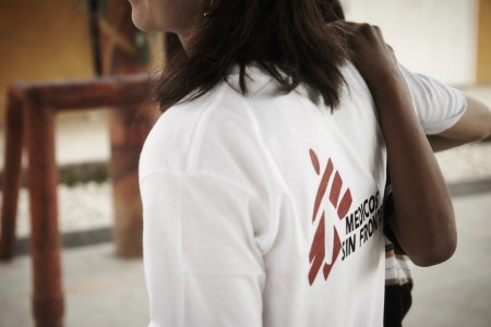 MSF psychologist helps a person to walk