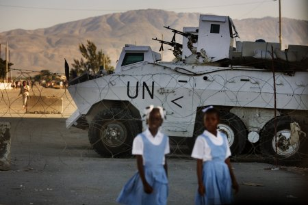 Two girls walk in front of a UN checkpoint in Haiti