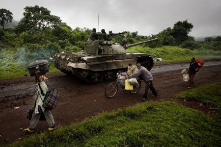 A tank moves towards the frontlines as people are fleeing