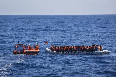 Lifejackets are distributed to 129 people in a rubber boat by an MSF rib in international waters off the north coast of Libya, on June 8, 2017.