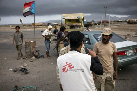 MSF team in Aden's streets. An MSF staff is speaking with armed men at a check point.