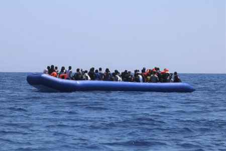 A group of people in distress in a rubber boat before being rescued.