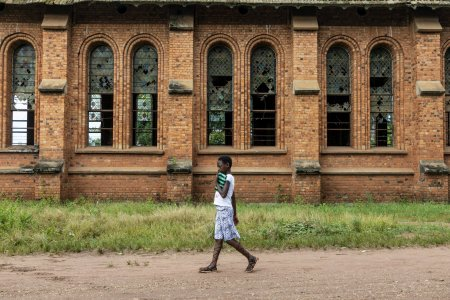 A girl walks next to the church of Mayi-Munene, destroyed by the last conflict that affected the region the recent years.